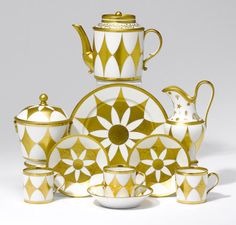 LOT 396 A Paris tea service Circa 1790-1810. Decorated in gold with a large chequered pattern comprising a teapot and cover, milk jug, sugar pot and cover, plate and six cups and saucers, teapot 14cm high, G.h. Rue Thirou à Paris in iron-red to the base (18)