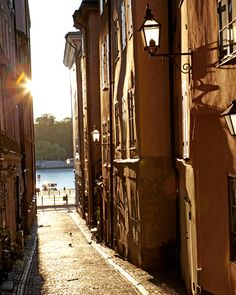 A sunlit sliver of an alley provides a view of the Grand Hôtel across the Norrström River.