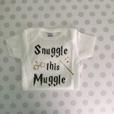 A onesie with the saying Snuggle this Muggle First picture shows glitter black and gold wording and images. Second picture shows plain black and yellow.