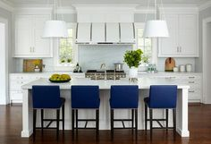 Royal blue counter stools provide a comfortable, low-profile perch at a white kitchen island offering a contrast of light and dark with a tranquil vibe.