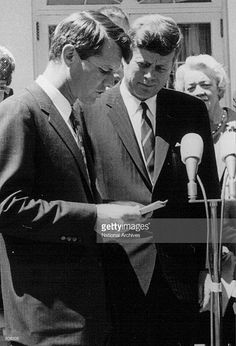 President John F. Kennedy listens as his brother Robert speak at a White House ceremony May 7, 1963.