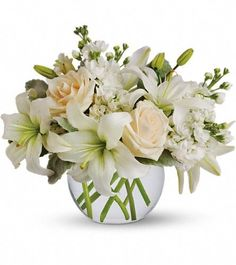 Crème roses, white asiatic lilies and stock stem are incredibly arranged in a bubble vase. Description from classicfloristandhomedecor.com. I searched for this on bing.com/images