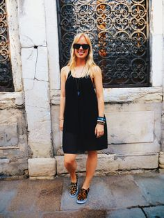 @sammydress black swing dress, @debshops shops leopard print slip on sneakers, @swallowheart titanium quartz geometric pendent, @kameleonz sunglasses, boho jewelry, boho outfit, hippie outfit, travel outfit, venice