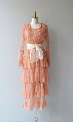 Antique 1910s Edwardian coral lace dress with long cutout lace sleeves, lace modesty panel, wide waist with wrapped cream sash, tiered lace skirt and metal hook and eye clasps. A slip is necessary, not included.   --- M E A S U R E M E N T S ---  fits like: extra small bust: best fit 32-34 waist: 25 hip: best fit up to 38 length: 52 brand/maker: n/a condition: good, minor tears throughout to ensure a good fit, please read the sizing guide: http://www.etsy.com/shop&#x2...