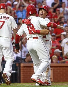 Jon Jay congratulates teammate Kolten Wong on his two-run home run during the third inning of a baseball game against the Cincinnati Reds. Cards won the game 8-4. 9-20-14
