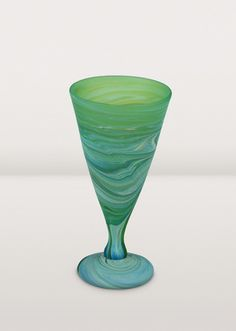 Vivid colours swirl across this goblet, hand-blown by artisans of Hebron Glass & Ceramic Factory. Recycled bottles are smashed into pieces and melted in high temperature ovens. In Phoenician glass blowing, artisans add substances to the molten glass, with the resulting reaction creating a range of colours. Working with this process takes an especially skilled hand and is reserved for the true masters of the art. Each piece has its own unique blend of colour and pattern.