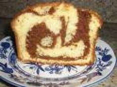 Receita de Bolo marmorizado - 100 g de manteiga, 1 xícara de açúcar, 3 ovos, 1 xícara de leite, 2 xícaras de farinha de trigo, 2 colherzinhas de essência de baunilha, 50 g de chocolate em pó ou ralado, 1 colherzinha de fermento em pó, forma untada e levemente enfarinhada