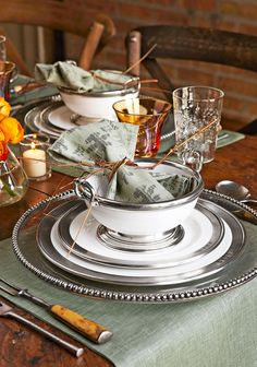 """Tesoro"" glass chargers with beaded rims are by Arte Italica. Pewter-rimmed ceramic dinner and salad plates are ""Convivio"" from Match. - Traditional Home ® / Photo: Tyllie Barbosa"