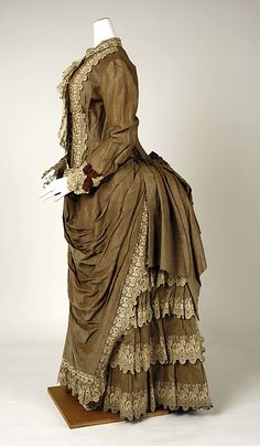 Victorian haute couture fashion dress gown from American designer Gomer Herbert in 1883. Made from cotton, embroidery lace and trim embellishment. A modern representation of women clothing throughout the #historical #19th century. Although the silhouette remained the same incorporated menswear affectation into both ornamentation and construction with decorated high neck, bodice and sleeves. The ruffle skirt drape gather with bustle at the back. #hautecouture #couture #vintage #victorian #fashion
