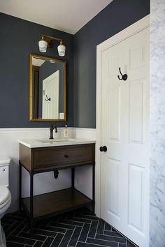 murs de bain moitié en gris fumée, moitié en blanc, porte blanche avec crochet pour accrocher le linge en noir, luminaires en blanc avec partie métallique en couleur or, carrelage en gris fumée, avec des fugues blanches, meuble rangement vintage marron foncé avec pieds métalliques en noir
