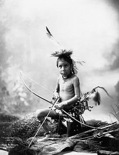 +~+~ Antique Photograph ~+~+  Native American boy named Pulls the Bow in headdress and a decorated loincloth holding a bow and arrows.  Ca. 1900.