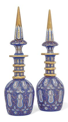 A PAIR OF BOHEMIAN CLEAR-FLASH WHITE AND BLUE-OVERLAY CUT-GLASS DECANTERS AND STOPPERS  LATE 19TH CENTURY.  Made for the Persian market, cut with shaped panels, gilt with scrolls and applied with gilt glass 'jewels'