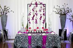 Zebra and pink flowers create a chic wedding table arrangement!