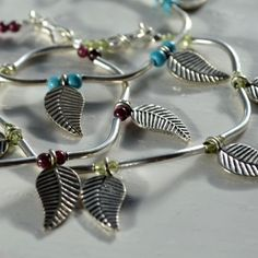 Fine Silver Charm Bracelet - High quality fair traded silver jewellery handcrafted by a hill tribe community in remote Northern Thailand. Flat leaf shaped silver charms are teamed with smooth tubular curved beads and gemstone beading. Clasp fine silver. 3 gemstone colourways to choose from; Peridot (pale green) Garnet (dark red) and Turquoise (pale blue).
