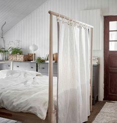 Nærbillede af en sengegavl med et stykke tekstil brugt som rumdeler.