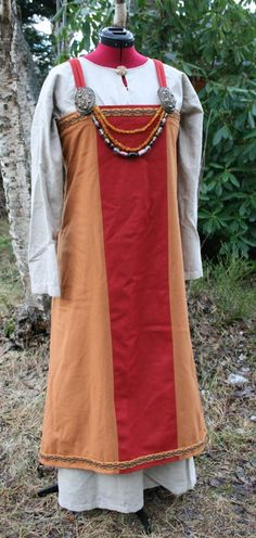 From bloggfiler.no.  Interesting--the effect of a front cloth achieved with a contrasting color panel that is part of the apron dress.