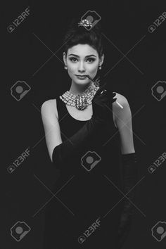 https://previews.123rf.com/images/svetography/svetography1508/svetography150800046/43550325-Beautiful-woman-looking-like-Audrey-Hepburn-standing-with-cigarette-holder-Stock-Photo.jpg