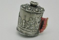 A silver tape measure embossed with a relief of Abbotsford House.