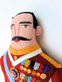 Mimi Kirchner: General with Medals Doll. $309.50 AUD. This heroic fellow is made of wool. He has pink skin color and a big mustache. He is wearing a red tunic with lots onef (wool) felt medals and a sash. His pants are blue and he is wearing high black boots. His face and hands are hand embroidered. He has applied ears.    Original design, wool Man doll with embroidered face. Stuffed with high quality polyester fill. He is 24 1/2 inches (62cm) tall to the top of his hair.