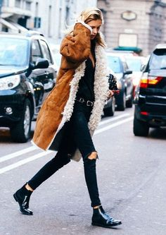 Ripped black jeans with booties and a shearling coat.