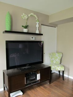 Shelf with florals a picture frames above tv in livin room a must!!!