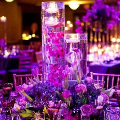 tulips, roses, and orchids submerged. with candle on top