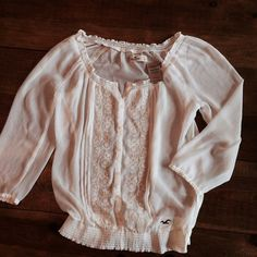 Hollister Sheer Blouse with Floral Stitching Beautiful Hollister Sheer Blouse with Floral Stitching and button up front. Elastic waistband. 100% polyester. Brand with tags never worn. Hollister Tops Blouses