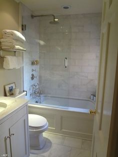 Partial glass door on tub/shower with drop in tub featuring marble top and wood wainscoting.