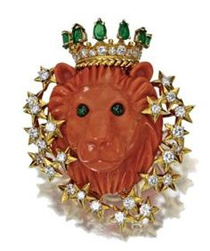 And so we'll end today with the king of beasts. The back of this coral lion with emerald eyes also has a two-prong hairpin form. The lion wears a crown set with diamonds and emeralds and is wearing a diamond necklace. Signed Tiffany & Co, numbered 17710.