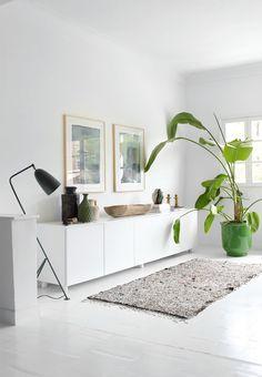 Botanical interior in the bright living room. We love the Grasshopper Floor Lamp from Gubi.
