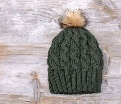 Womens Slouchy Cable Knit Beanie Hat in Deep Forest Green with a Camel and Brown Faux Fur Pom Pom This hat is hand knit from a dark green yarn and