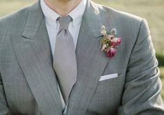 pink and purple boutonniere with grey suit and tie