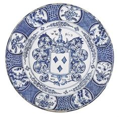 A LONDON DELFT DATED ARMORIAL BLUE AND WHITE CHARGER  1673  Of exceptionally large size, the central arms surrounded by scrolling foliage mantling with the initials W/W.M and the date 1673 flanking the crest and with MAY THE: 21TH below, the well with scroll-ornament and the broad rim with alternating panels of flowers and foliage and Oriental figures among rockwork and grasses, divided by waisted panels of scale and diaper-ornament, the underside with a white tin glaze  22 3/8 in. diameter