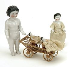 """Germany, ca. 1890, lot includes all china doll with nicely detailed molded hair, blue painted eyes, clenched fists with nicely detailed body, smaller all china doll with molded features (chipped toe), and 2 small Frozen Charlottes riding in a rattan cart Size: largest 5"""" t."""