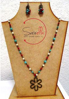 Engarzado en oro viejo con piedras en turquesa, rojo y hueso, dije de flor; incluye aretes.