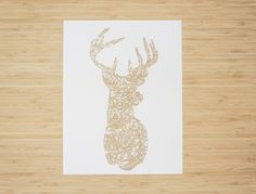 A Delicate lasercut design of a deer head with floral pattern. Each Light and Paper design begins as an original illustration, and is handcut with an x-acto knife. The design is then scanned and converted to lasercut each individual print.