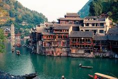 The ancient city of Fenghuang in Hunan Province in China. The town, with its picturesque bridges and unique houses on stilts is so well-preserved it's like stepping back in time!