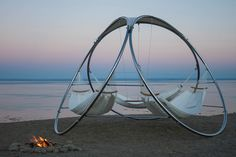 A weatherproof hammock concept with three suspended hammocks and a teak table that turns the traditional hammock into a thing of the past.