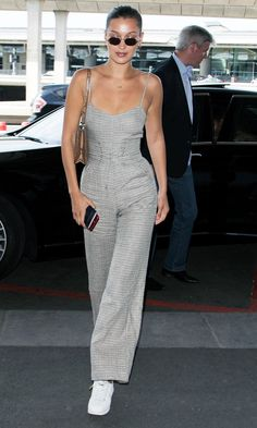 At the airport in Paris, Bella Hadid wore a grey jumpsuit with corset belt and Nike Cortez trainers. Click here to see and shop her look.