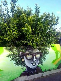 Many times, artists will incorporate nature into their street art because the two naturally interact. This artist chose to use a shrub to help create the afro of this woman.