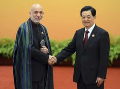 Chinese President Hu Jintao (R) greets Afghanistan President Hamid Karzai at the Shanghai Cooperation Organization (SCO) summit in the Great Hall of the People in Beijing June 7, 2012.