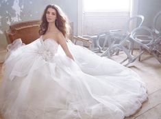 Jim Hjelm. Ivory Tulle over Creme satin faced taffeta Bridal Ball Gown, Crystal embroidered Tulle bodice, strapless sweetheart neckline, natural waist accented with horsehair bow, cascade skirt with horsehair edged detail, chapel train.