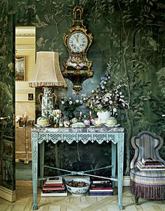 Secret door, reminiscent of Pauline de Rothchild's well-photographed Chinoiserie walled room, where she peeks in the door for the camera. Hand painted wallpapered room here, at Howard Slatkin's  NY apt. Interesting antique table from a winter garden | via New York Magazine | photo by Tria Giovan