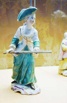 Jägerin  Der Figur des Jägers entspricht die der Jägerin, die standesgemäß in ein grün-weißes Kostüm gekleidet ist und auf dem Kof einen modischen Dreispitz, ebenfalls grün, trägt.