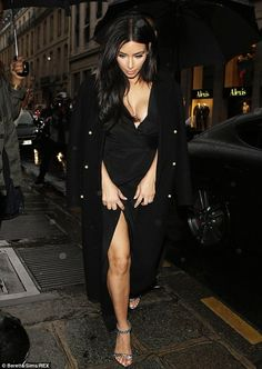 Don't rain on my parade! Kim Kardashian lifts her dress revealing a thigh-high split as she tries to avoid getting the dress wet as she is flanked by bodyguards holding up umbrellas in Paris