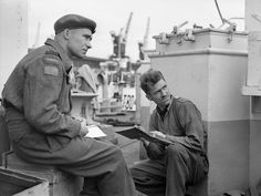 Lieutenant John MacIsaac (left), 14th Field Regiment, Royal Canadian Artillery (R.C.A.), discussing D-Day fire plan tactics with Bombardier Charles Zerowel aboard a Landing Ship Tank, Southampton, England, 4 June 1944 June 4, 1944. Library and Archives Canada MIKAN 3526089