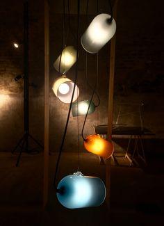 V8 Designers  - PROJO -  Lampe en verre soufflé, CIAV, prototype 2013  Un réflecteur en verre coloré, sablé à l'intérieur et une attache de verre posée comme une anse - permettant de diriger le faisceau lumineux : le minimum pour mettre sous les feux de la rampe la soupe du dimanche soir