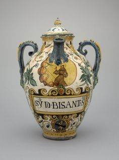 "Spouted drug jar with handles. Earthenware covered with presumed tin glaze (not the foot). Painted with grotesques including music-making men with tails. Beneath the spout is St Francis receiving the stigmata. Beneath, on a white tablet ""SYo Di BISANTI Sce"". Also a shield of arms for Boni or Buoni (?): blue a lion rampant yellow charged on the shoulder with a red fleur-de-lis, over all a bend black; flanking the shield ""SR""."