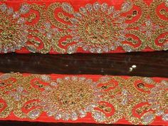 Red color handmade fabric trim. It is embellished with gold color braid work.This border has been made using silk, jari gota and sequins.  This stunning lace can be used for designing stylish...