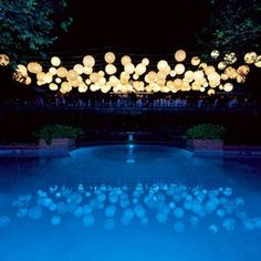 Magical cluster of lanterns over pool.